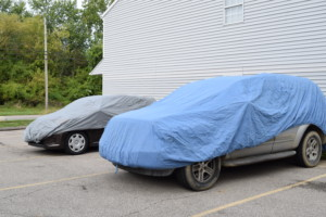 Covering nearby vehicles with car covers during the project