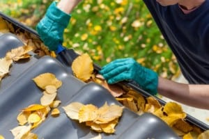Man-cleaning-the-gutter-from-autumn-leaves-300x200 Commercial Gutters: Why are they important and how to maintain them