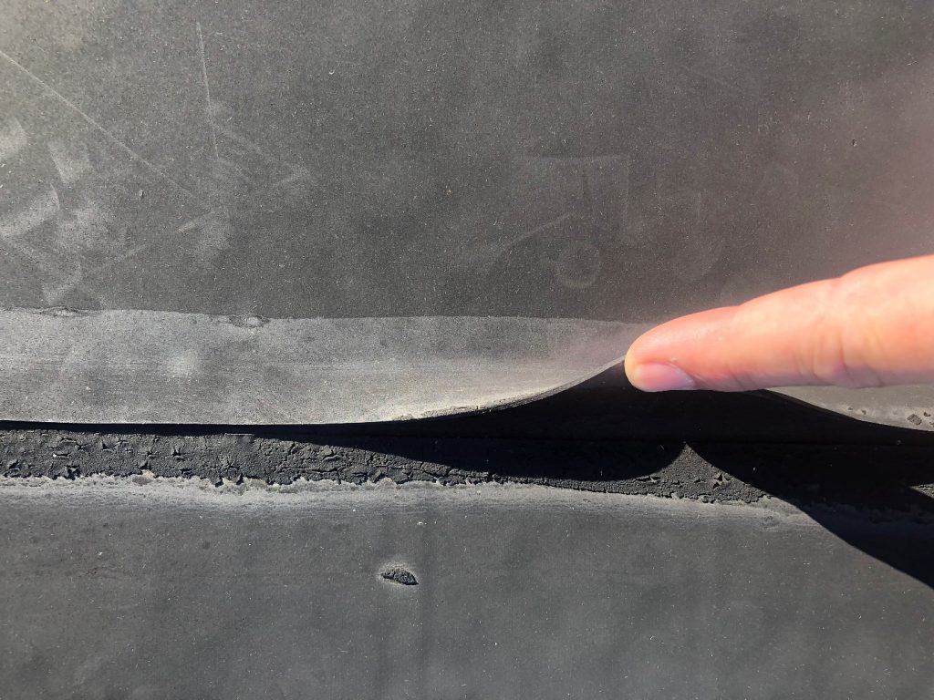 Seam separation of a rubber roof. An invitation for water penetration that will cause a roof leak.