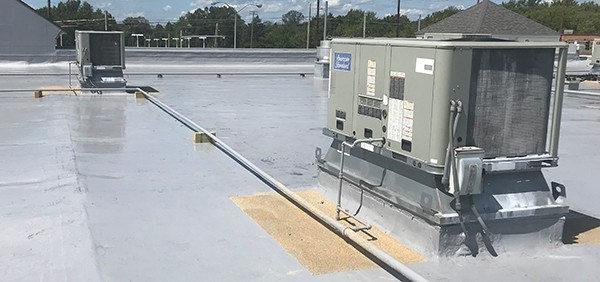 Sand embedded walkways to designate walking areas on a silicone restoration roof