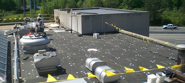 Coverboard being put down over a TPO roof