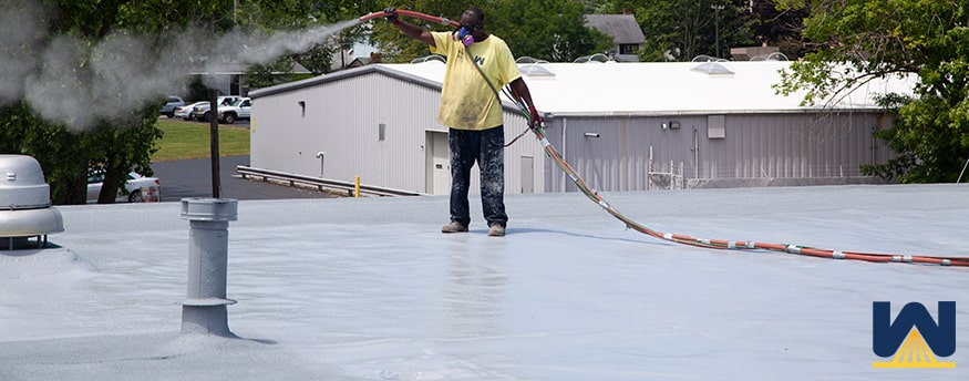 roofer adding granules to a spray foam roof