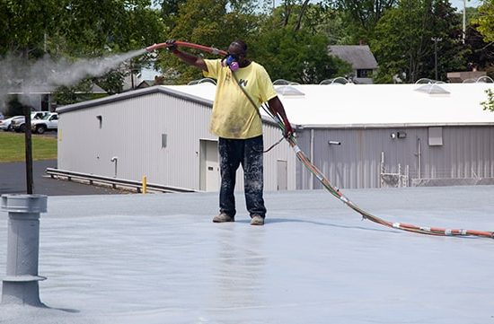 roofer spraying granules onto a spray foam roof