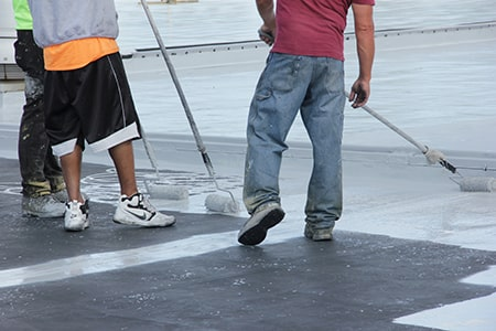 roof coating application after seams have been treated